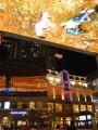 insane shopping complex with giant overhead 'movies'